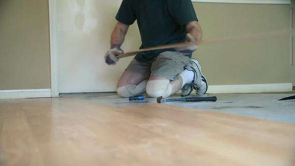 A worker removing old laminate flooring in preparation of new floor covering or homeowner engaged in a DIY project. Royalty-free stock video