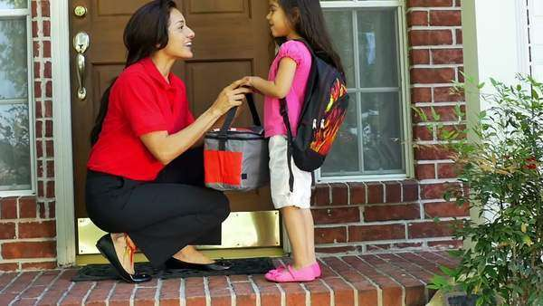 A little girl wearing a backpack gives her mother a little kiss after getting her lunch bag and a cheerful send off to school. Slow motion. Royalty-free stock video