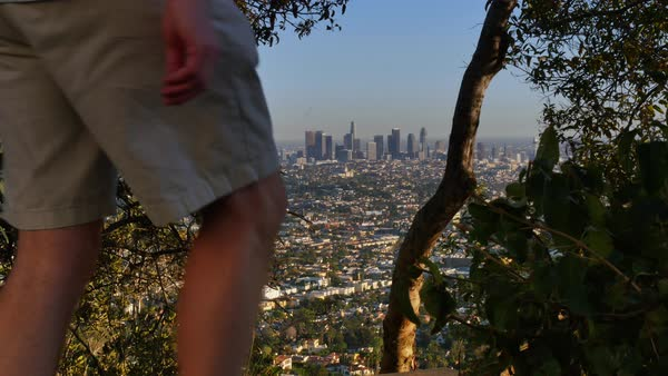 The skyline of Los Angeles is seen in the distance while a hiker walks the paths in the Hollywood hills.    Royalty-free stock video