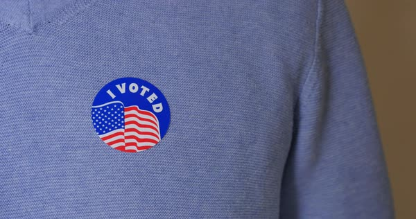 A man places an I Voted sticker on his chest after voting.  	 Royalty-free stock video
