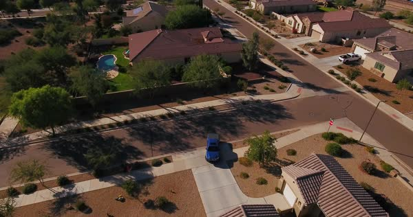A flyover aerial establishing shot of a typical Arizona residential neighborhood as a vehicle leaves a driveway. Phoenix suburb.	 	 Royalty-free stock video