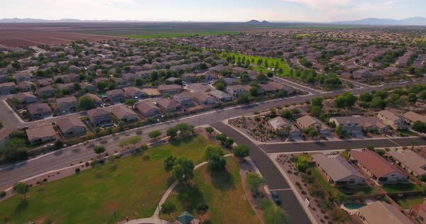 A flyover aerial establishing shot of a typical Arizona residential neighborhood and playground. Phoenix suburb.	 	 Royalty-free stock video