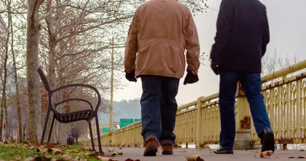 Low angle shot of two men walking outside away from camera in downtown Pittsburgh on a cold winter day.    Royalty-free stock video