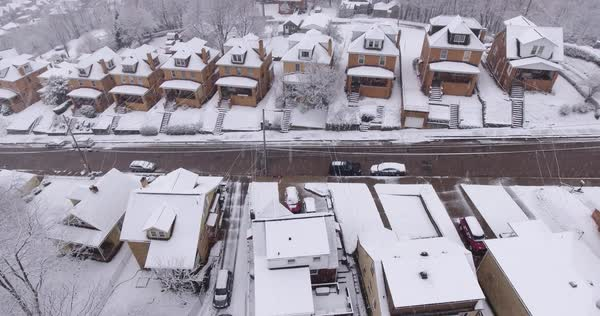 A slowly moving forward aerial winter view of a typical Western Pennsylvania rust belt residential neighborhood in a snowstorm. Royalty-free stock video