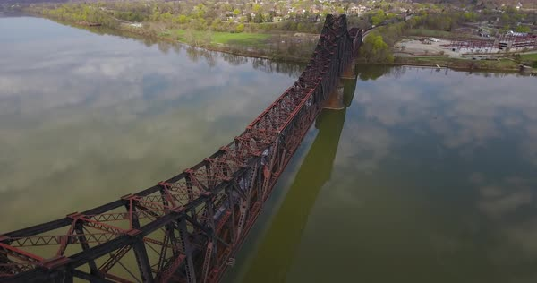 MONACA, PA - Circa April, 2017 - A daytime aerial reverse view of a cargo train traveling on a railroad bridge over the Ohio River in Western Pennsylvania.  Royalty-free stock video