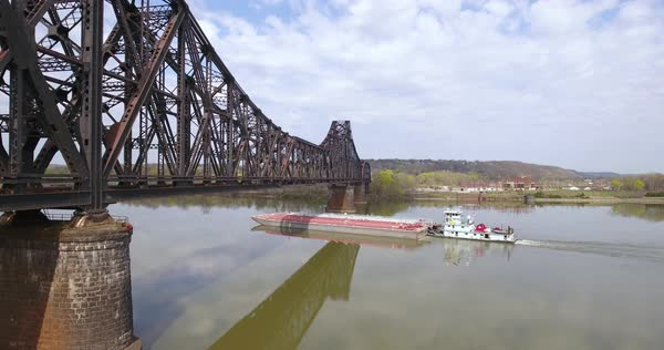 MONACA, PA - Circa April, 2017 - Aerial view coal barge travels down the Ohio River in Western Pennsylvania under a railroad bridge. Royalty-free stock video