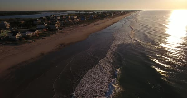 An early morning reverse aerial establishing shot of the houses along Topsail Island on the Atlantic Ocean in North Carolina. Royalty-free stock video