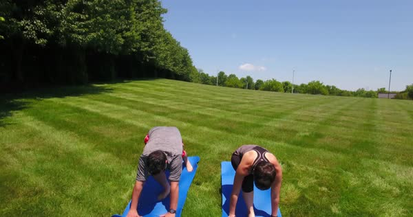 Two young people perform the warrior yoga position outside on a sunny day. Dramatic rising dolly up shot. Royalty-free stock video
