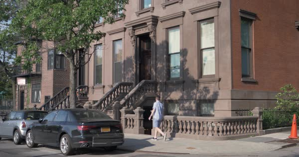 A daytime exterior establishing shot of a typical Brooklyn brownstone residential home.  Royalty-free stock video