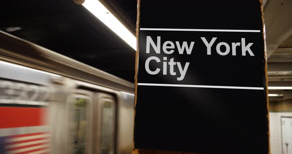 A Manhattan subway leaves the station near a hypothetical New York City identification sign on a pillar. Royalty-free stock video
