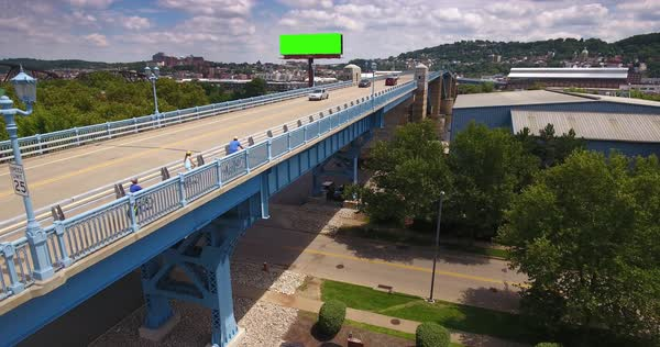 A slow reverse aerial establishing shot of traffic and bicyclists on the 31st Street Bridge in the Lawrenceville area of Pittsburgh. Green screen billboard for customization. Royalty-free stock video