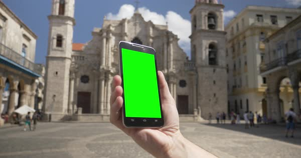 Holding a green screen smartphone in portrait mode outside Havana Cathedral. Royalty-free stock video