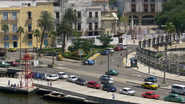 A high angle aerial tracking dolly establishing shot of traffic on the streets of Havana, Cuba, including colorful vintage American cars that are a popular tourist attraction. Royalty-free stock video