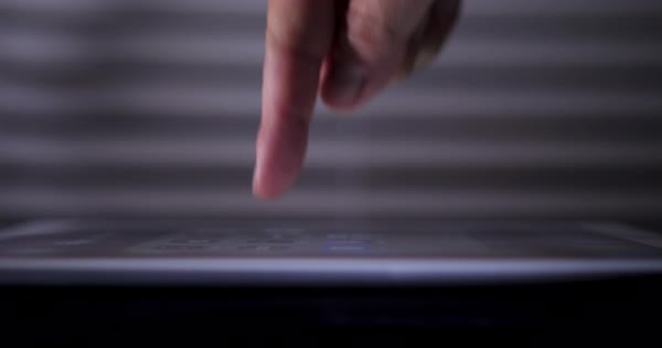 A profile close-up with shallow DOF of a finger pressing a button on a touchscreen tablet PC. Royalty-free stock video