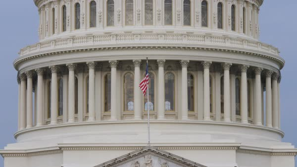 An extreme close up shot of the Capitol Dome with the American Flag blowing in the wind.   Royalty-free stock video
