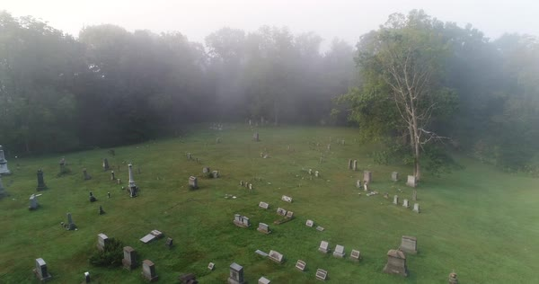A forward high angle aerial above a historic cemetery in the foggy woods.  Royalty-free stock video