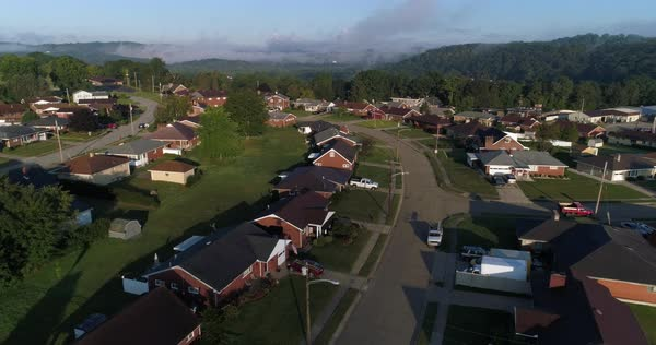 An aerial flyover of a typical Western Pennsylvania residential neighborhood on an early foggy autumn morning.   Royalty-free stock video