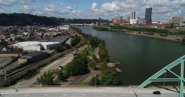 PITTSBURGH, PA - Circa September, 2017 - A high angle aerial profile left to right establishing shot of traffic passing on the Birmingham Bridge over the Monongahela River.   Royalty-free stock video