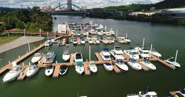 A low angle forward moving aerial establishing shot of a boating marina on the Monongahela River with the Pittsburgh skyline in the distance.   Royalty-free stock video