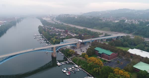 A high angle aerial early morning foggy establishing shot of Washington's Landing, a small island on the Allegheny River in Pittsburgh, Pennsylvania.  Royalty-free stock video