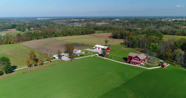 A slow rising aerial establishing shot of a typical New England farm on an early autumn day.   Royalty-free stock video