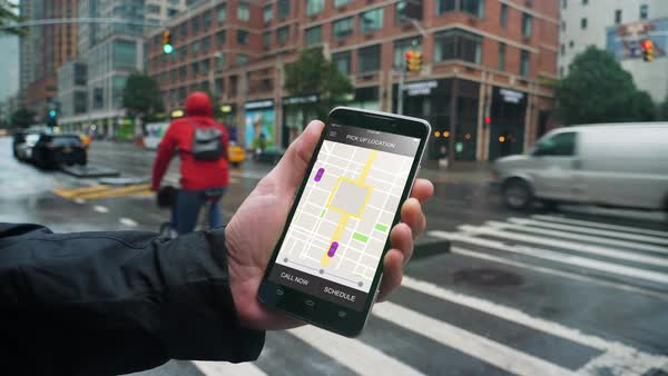 A man uses his smartphone to observe ride sharing traffic patterns on an interactive map in a fictional city on a rainy day.   Royalty-free stock video