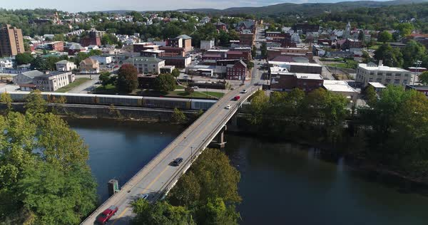 A slowly moving forward aerial shot of the small town of Connellsville, Pennsylvania while traffic travels on the Officer McCray Rob Memorial Bridge over the Youghiogheny River. Pittsburgh suburbs.   Royalty-free stock video