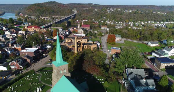 A morning high angle orbiting aerial establishing shot of the small town of Brownsville, PA - a Pittsburgh suburb. Bridges over the Monongahela River in the distance.   Royalty-free stock video
