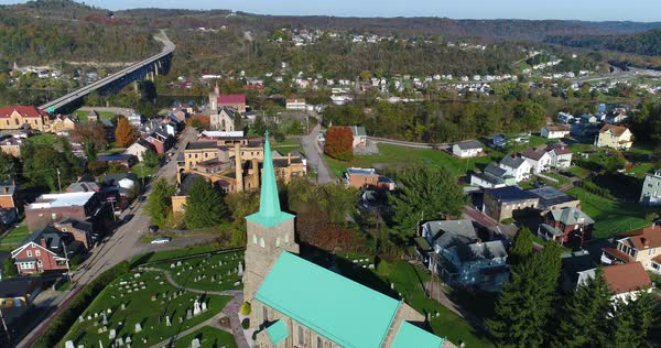 A reverse high angle rising aerial establishing shot of the small town of Brownsville, PA - a Pittsburgh suburb. Bridges over the Monongahela River in the distance. Royalty-free stock video