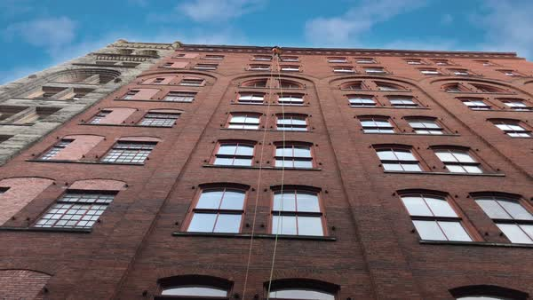 Looking up at a window washer hanging from ropes on the side of a tall red brick building. Royalty-free stock video