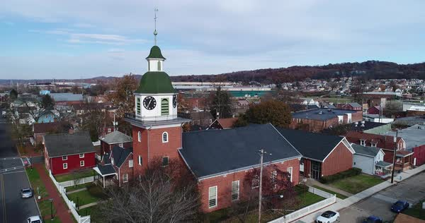A daytime exterior aerial shot of a small town's church and steeple in the late Autumn.   Royalty-free stock video