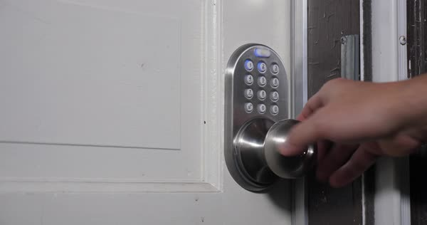 A homeowner enters a passcode on the door for entry.   Royalty-free stock video