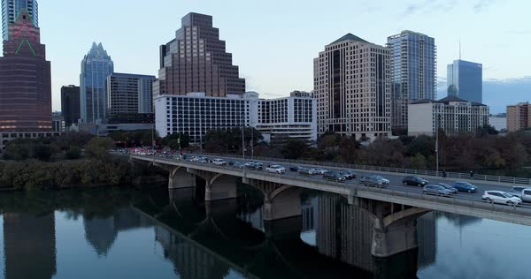 A slow reverse evening aerial establishing shot of traffic passing over the Congress Avenue Bridge on the Colorado River in Austin, Texas  Royalty-free stock video