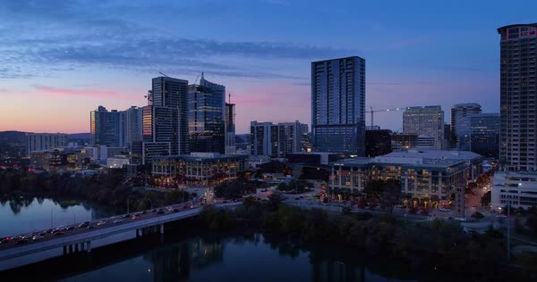A slow lowering reverse aerial establishing shot of the Austin, Texas skyline on an early Winter evening as traffic passes over the South 1st Street Bridge.   Royalty-free stock video