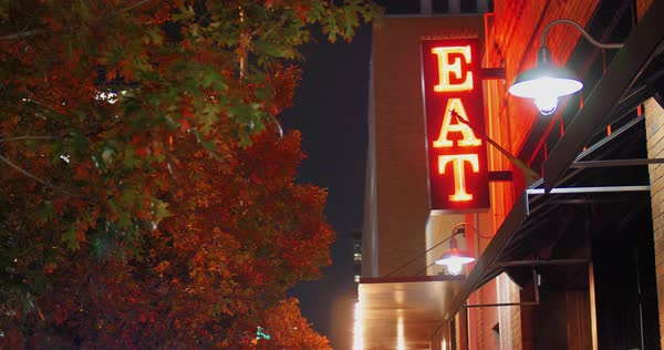 "A nighttime view of a red neon ""EAT"" sign on the side of a restaurant in a large city. Royalty-free stock video"