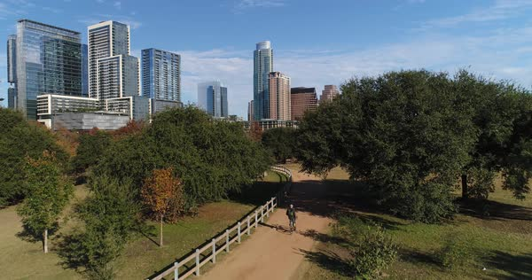 A daytime rising aerial dramatic view revealing the Austin city skyline as seen from Vic Mathias Shores Park as a bicyclist rides on a recreational trail.   Royalty-free stock video