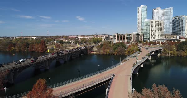 A slow forward rising aerial establishing shot (DX) of the Austin city skyline with the Pfluger Pedestrian Bridge over the Colorado River in the foreground on a late sunny Autumn day.   Royalty-free stock video