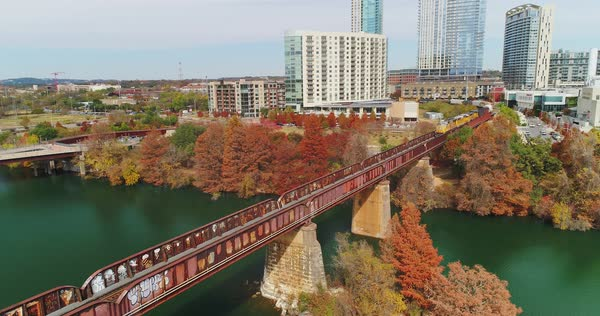 AUSTIN, TX - Circa December, 2017 - A slow forward aerial view of a train traveling on a bridge over the Colorado River in Austin, Texas with the city skyline in the distance.   Royalty-free stock video