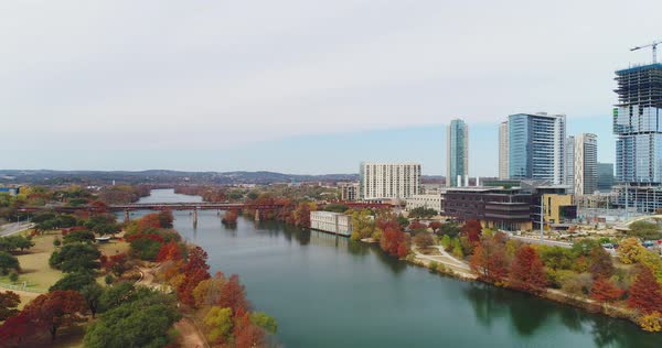 A slow reverse rising aerial establishing shot of the Austin, Texas skyline with the Colorado River in the foreground. Overcast late Fall day.   Royalty-free stock video