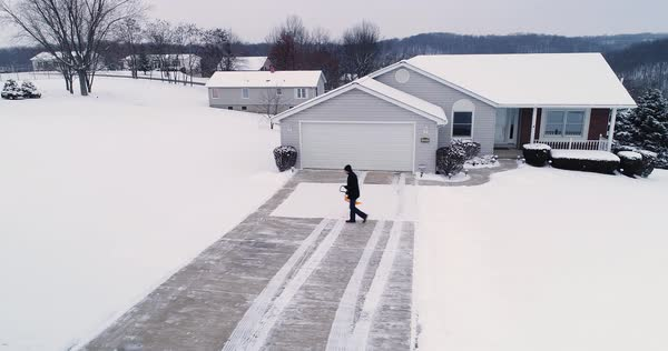 A low orbiting aerial view of a homeowner shoveling snow from the driveway at a home in a typical Pennsylvania neighborhood. Pittsburgh suburbs.   Royalty-free stock video