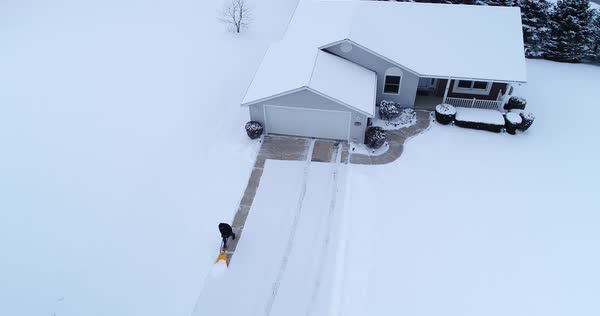 An aerial view of a homeowner shoveling snow from the driveway at a home in a typical Pennsylvania neighborhood. Pittsburgh suburbs.   Royalty-free stock video