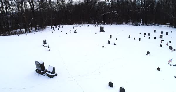 A slow reverse flyover of snow covered gravestones in an old Pennsylvania countryside cemetery.   Royalty-free stock video