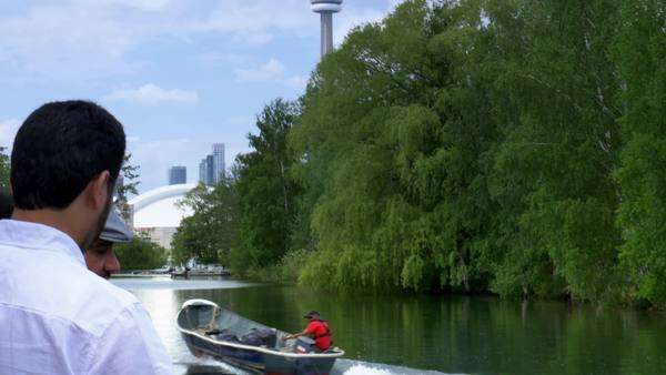 TORONTO, ONTARIO, CANADA - Circa June, 2014 - A fisherman heads out to Lake Ontario while tourists watch from a tour boat. Royalty-free stock video