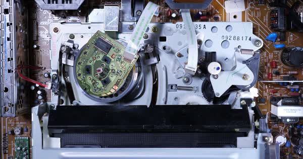 A top-down inside view of the electronics of a VCR as a VHS tape is inserted. Top off view.  Royalty-free stock video