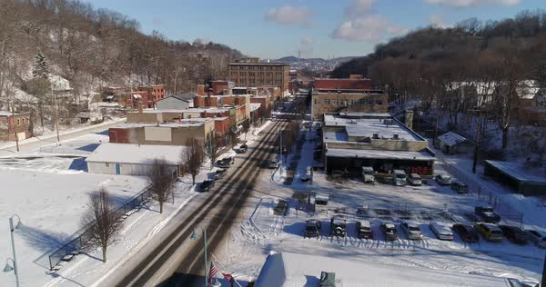 A slow reverse aerial establishing shot of the Aliquippa, PA business district after a winter snowfall. Pittsburgh suburb.  Royalty-free stock video