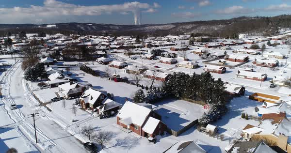 A slow reverse winter aerial establishing shot of snow covered roads and homes in a rust belt residential neighborhood. Pittsburgh suburbs.   Royalty-free stock video