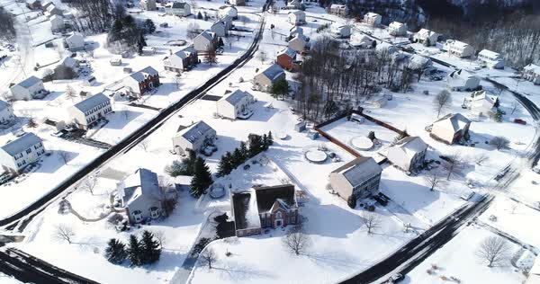 A slow forward tilt-up winter aerial establishing shot of snow covered roads and homes in a rust belt upscale residential neighborhood. Factory smokestacks in the distance. Pittsburgh suburbs.   Royalty-free stock video