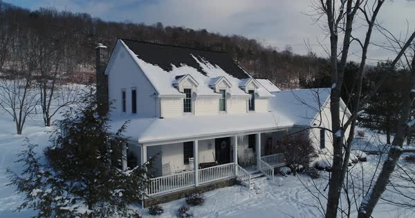 A slow aerial push establishing shot of a typical snow-covered Pennsylvania farmhouse in Winter.   Royalty-free stock video