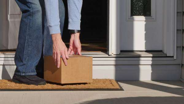 A man picks up a package from outside his front door. Royalty-free stock video