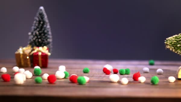 Christmas time decorations on a wooden table Royalty-free stock video - Hand Removing Christmas Decorations From A Wooden Table - Stock